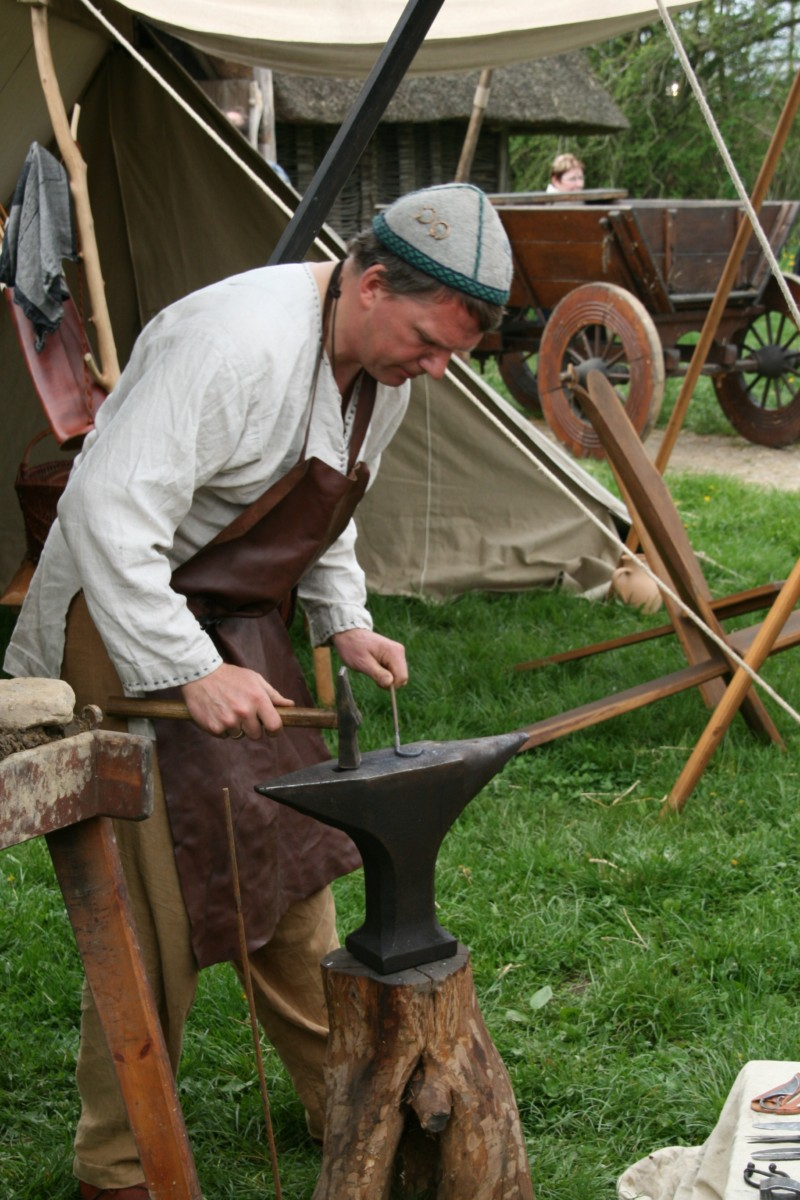 An adult working on a blacksmithing project