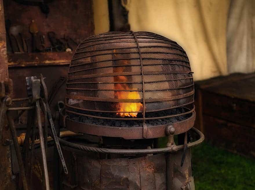 Brown blacksmithing forge in a backyard.