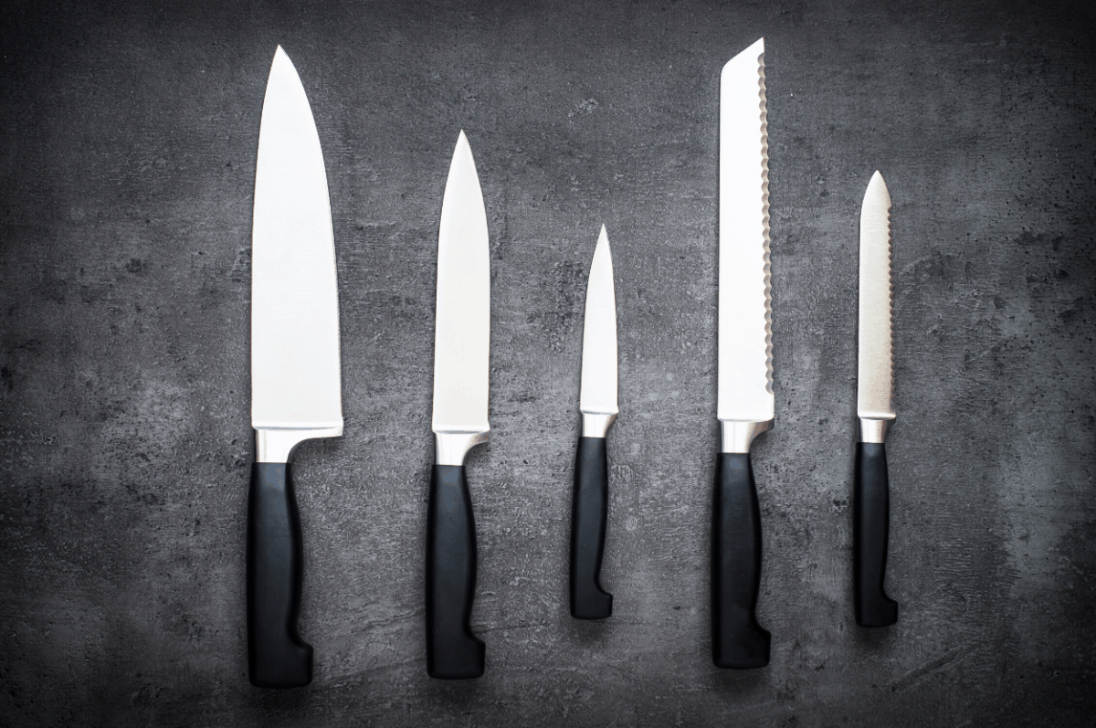 Five chef knives on a table.