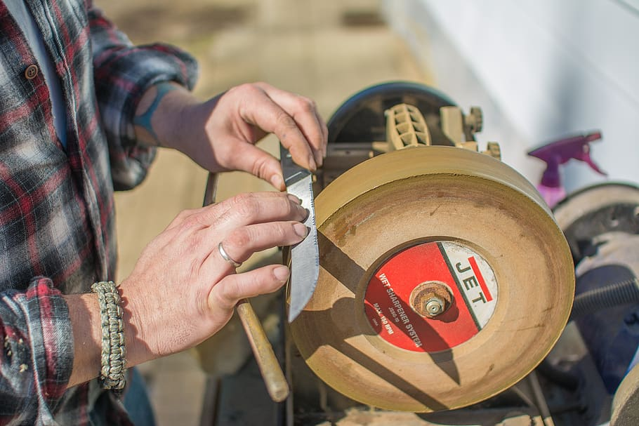 Person sharpening a knife with a whetstone.