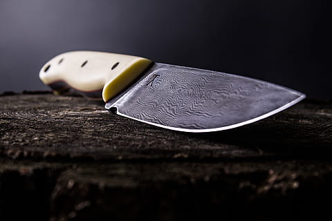A knife with a wooden handle and engravings.