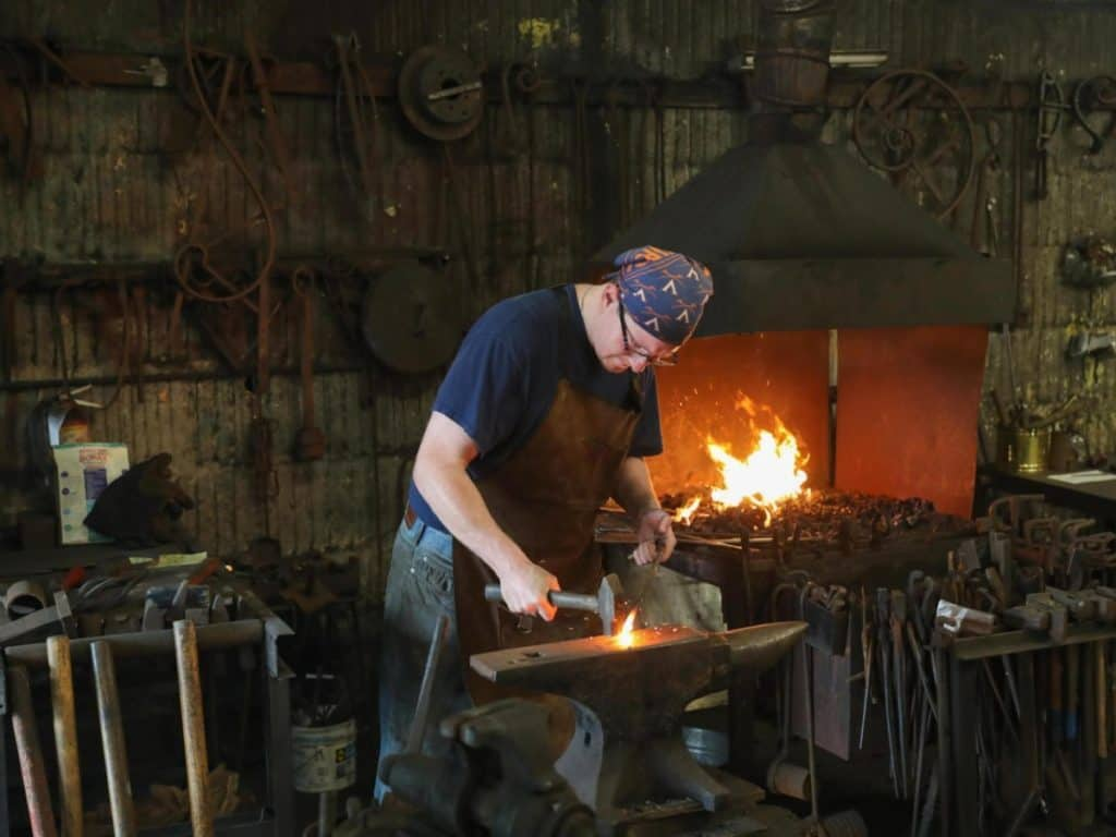 Person blacksmithing on an anvil.