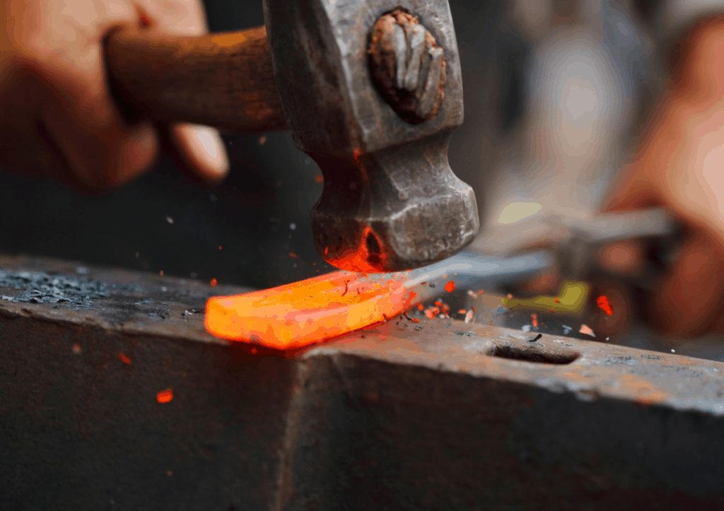 Hammer hitting a hot piece of metal on an anvil.