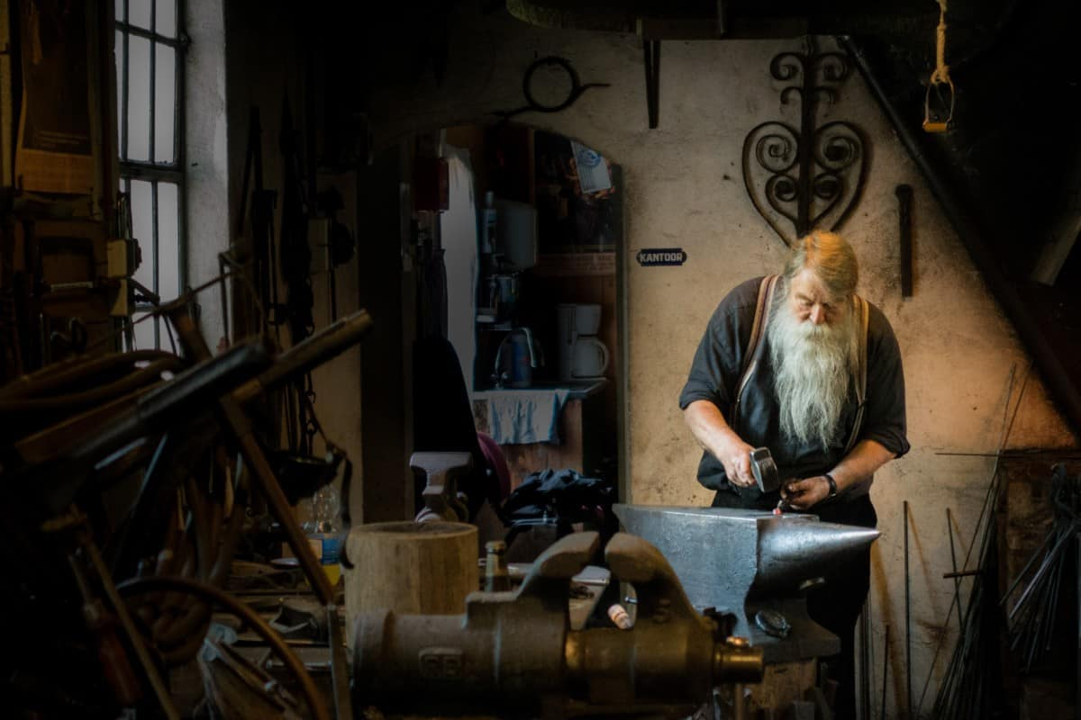 Blacksmith working on an anvil in shop.